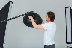 Man preparing lighting equipment - stock photo