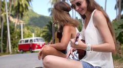 Boho Hippie Women with Guitar Hitchhiking on Road in Summer Stock Footage