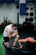 Trainer assisting a woman doing push ups on a bosu ball Stock Photos