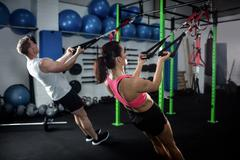 Man and woman doing suspension training with trx fitness straps Stock Photos