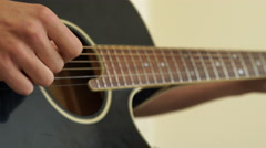 4K close up of Guitar strings on black guitar being played by caucasian fingers Stock Footage