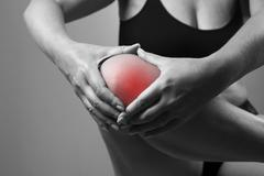 Pain in the knee. Pain in the human body on a gray background - stock photo