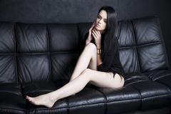 Beautiful young woman in bodysuit with long legs and long black hair - stock photo