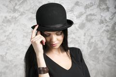Portrait of a beautiful young woman in a black dress and bowler hat - stock photo