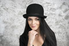 Portrait of a beautiful young woman in a black dress and bowler hat Stock Photos