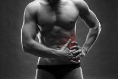 Pain in the left side. Muscular male body. Handsome bodybuilder posi - stock photo