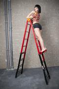 Beautiful young sexy woman in red high heels posing with construction equipme - stock photo