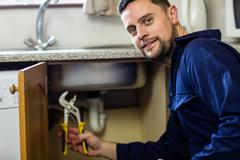 Portrait of plumber repairing a sink Stock Photos