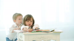 Little children play with pencils. Boy and girl are drawing near the window - stock footage