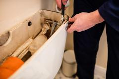 Plumber repairing a flush tank Stock Photos
