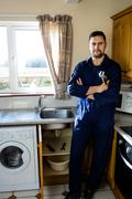 Portrait of plumber standing in kitchen Stock Photos