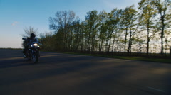 Motorcycle rides on the road, at the low point shooting Stock Footage