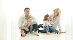 Happy family dad mom girl and boy sitting on the floor. - stock footage