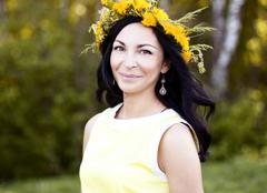 Beautiful brunette woman fashion style outdoors in yellow dress smiling happy - stock photo