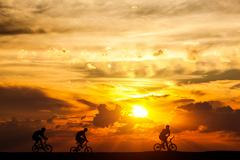 Friends on a bike trip at sunset. Active lifestyle, cycling hobby. Stock Photos