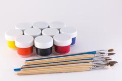 Gouache and brush on a white background Stock Photos