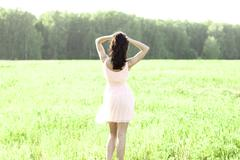 The girl pink dress is jumping meadow summer, happiness concept idea of fun - stock photo