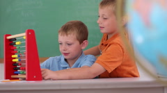 Two boys at school counting with abacus Stock Footage