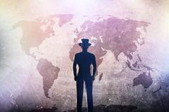 Silhouette of a man in hat standing in front of world map on grunge concrete  - stock photo