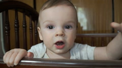 Little boy in a crib and pulls hands to the camera Stock Footage