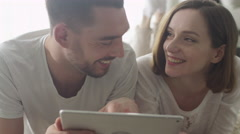 Man and Woman laying on Floor and using Tablet for Entertainment. Stock Footage