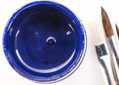 Jar with blue gouache and brushes on a white background closeup Stock Photos