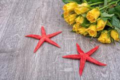 Red starfishes and roses on a wooden background - stock photo