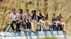 Group portrait of young people sitting together on van Stock Footage