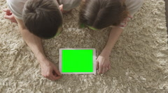 Mockup of People Laying on Floor and Using Tablet with Green Screen. Stock Footage