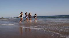Group of young women at beach run in surf Stock Footage