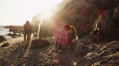 Group of young people at beach making camp fire Stock Footage