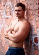 Young athlete bodybuilder man near brick wall Stock Photos