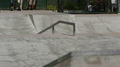 Skateboarder grinds rail at skatepark Stock Footage