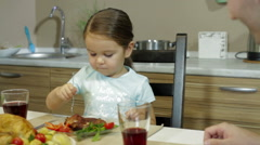 Serious Little girl having family dinner Stock Footage