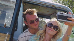Couple taking photos together with vintage camera on road trip Stock Footage