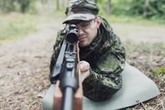 close up of soldier or hunter with gun in forest - stock photo