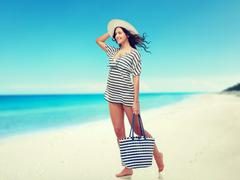 Stock Photo of happy young woman in summer clothes and sun hat