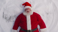 Santa Claus making a snow angel, closeup Stock Footage
