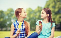 happy little girls eating ice-cream in summer park - stock photo