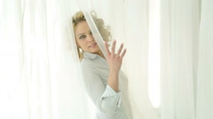 Beautiful girl in white shirt by the window among the white curtains. Stock Footage