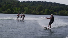 Three water skiers go off jump and one goes under Stock Footage