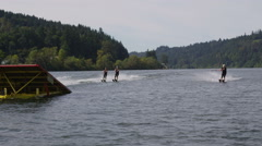 Water skiers go off jump Stock Footage