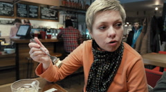 Blond short hair woman eats and talk to a friend Stock Footage