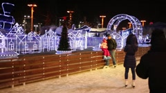 People skate on skating rink in evening at VDNKH along path Stock Footage