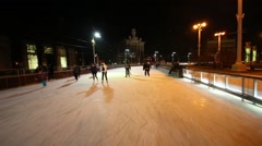 People slide along skating path in evening at VDNKH. Stock Footage