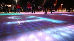 People skate on skating rink with ice surface illuminated from inside Stock Footage