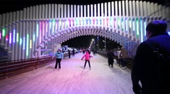 People slide along skating path under illuminated arch Stock Footage