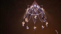 Actors on spinning metal framework made in shape of giant chandelier Stock Footage