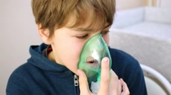Closeup face of boy breathing through nebulizer mask. Stock Footage