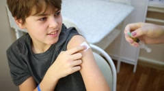 Female doctor prepares arm of boy to make injection. Stock Footage